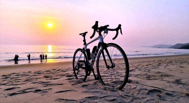 A bicycle and sunset at a beach