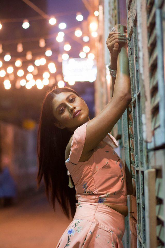 A stylish girl posing near a wall