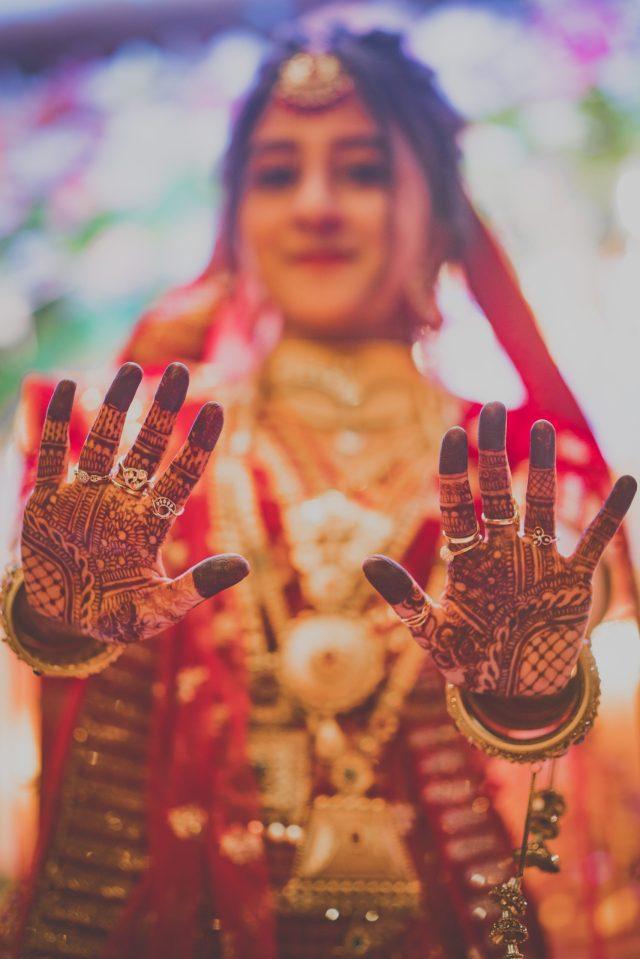 Bride posing with Mehendi in hand