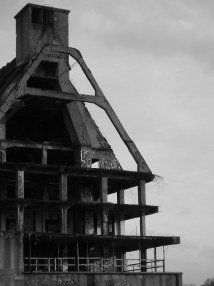 Schwarz-Weiß-Bild eines typischen Hafen-Speicherhauses, das teilweise nur noch als Stahlbetongerüst erhalten ist und so Blicke in sein Inneres gestattet.