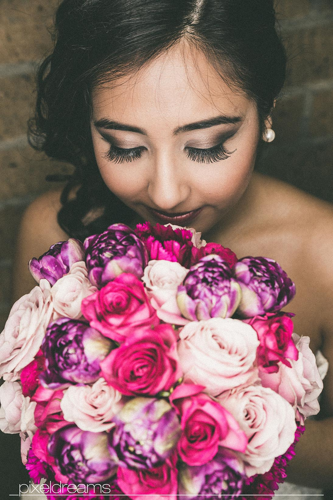 wundervolle pose der Braut mit ihrem Brautstrauß in rosa lila und pink, Braut Make up künstliche Wimpern und Brautfrisur im perfekten Einklang