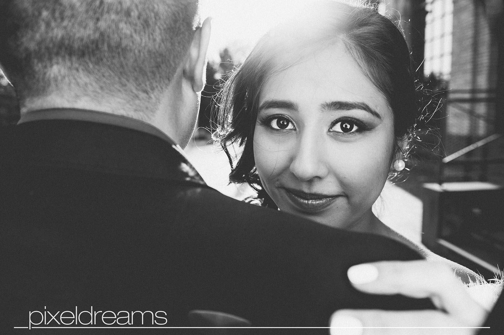 Perfektes Hochzeitsfoto im Gegenlicht der Sonne. Braut mit perfektem Braut Make Up posiert vor der Kamera für ihre Hochzeitsfotos im Schwarz Weiß Vintage sytle