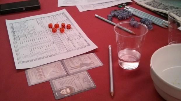 Tavolo coperto da un panno rosso sul quale sono appoggiate matite, un bicchiere di plastica con due dita d'acqua, tre carte, un foglio da compilare e una manciata di dadi rossi.