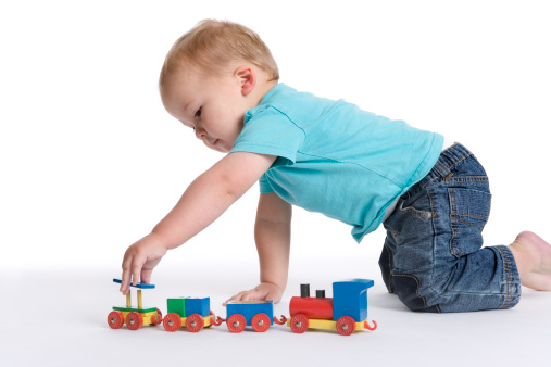 Toddler boy playing with a wooden toy train