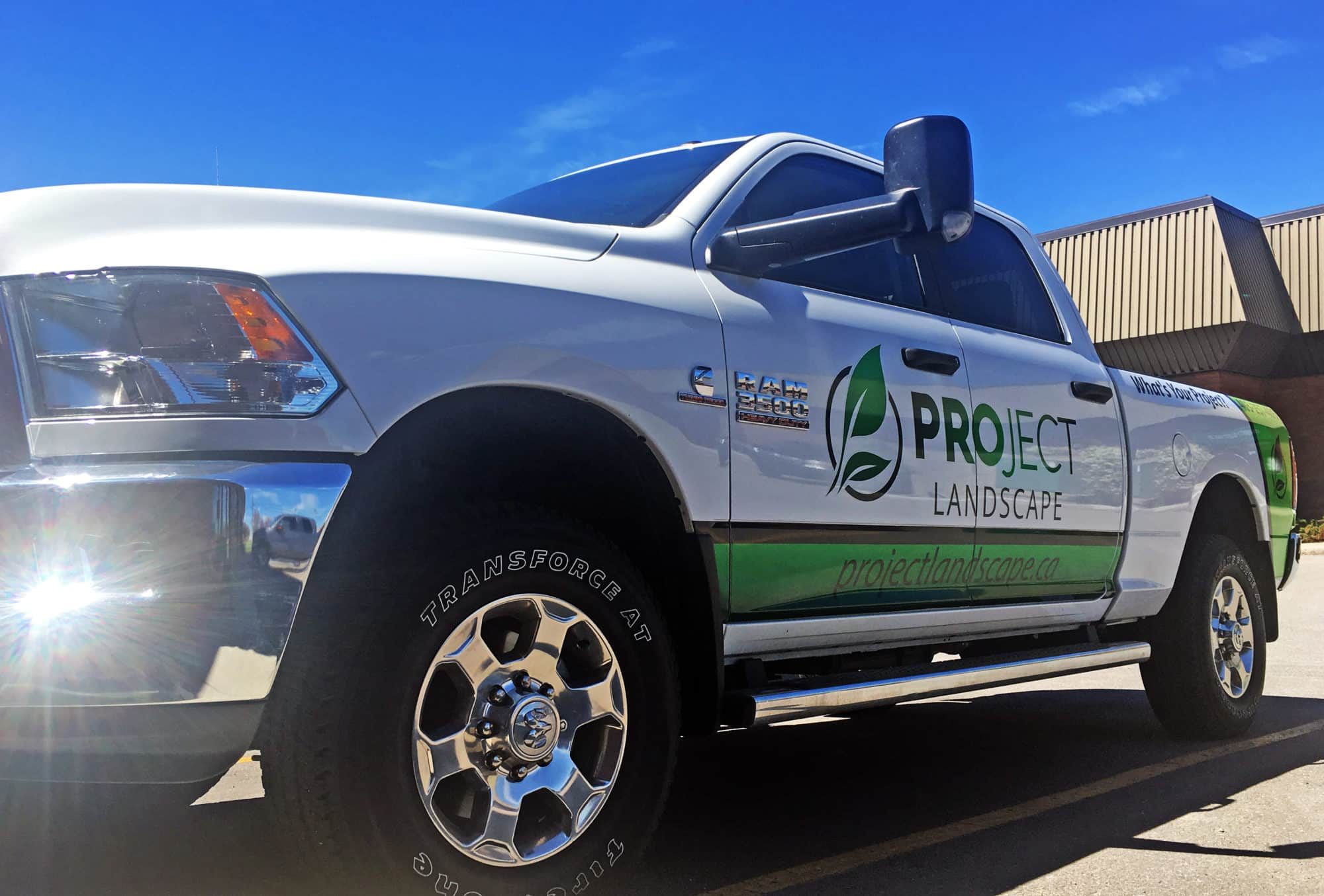A partial vinyl vehicle wrap, company logo decals, and phone number decals on a company work Dodge pickup truck.