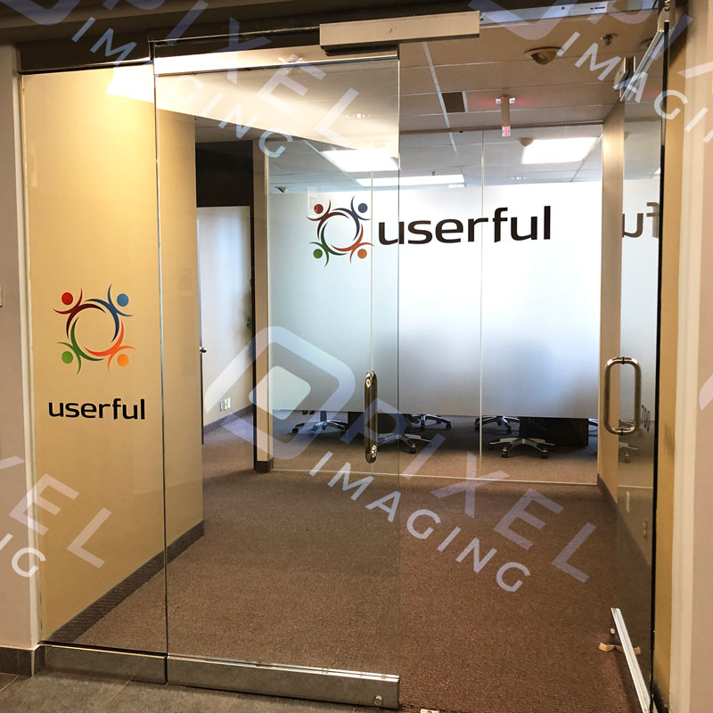 Custom-printed vinyl window decals and vinyl window lettering on a glass office door and glass wall divider.
