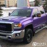 Pearlescent-purple vinyl vehicle wrap on a GMC 3500 HD pickup truck.