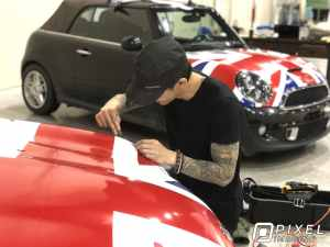 A man installing a custom-printed vinyl vehicle wrap of the United Kingdom Union Jack flag on two Cooper Mini cars.