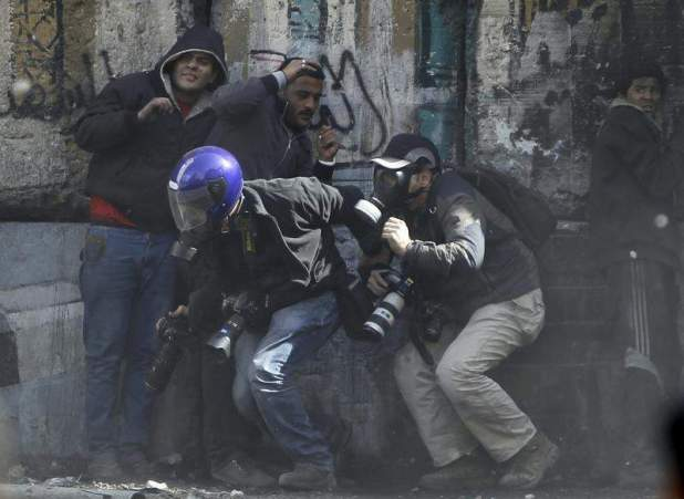 Photographers cower as protesters throw stones towards riot police along Sheikh Rihan street near Tahrir Square in Cairo January 25, 2013. REUTERS/Amr Abdallah Dalsh