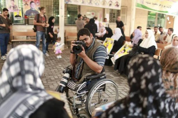 Wheelchair-bound Palestinian freelance photographer Moamen Qreiqea takes pictures of protesters calling for the release of Palestinian prisoners from Israeli jails, in Gaza City October 1, 2012. Qreiqea, 25, lost both his legs in an Israeli air strike in 2008 while taking pictures east of Gaza. The father of two is determined to continue his career despite his disability. REUTERS/Suhaib Salem