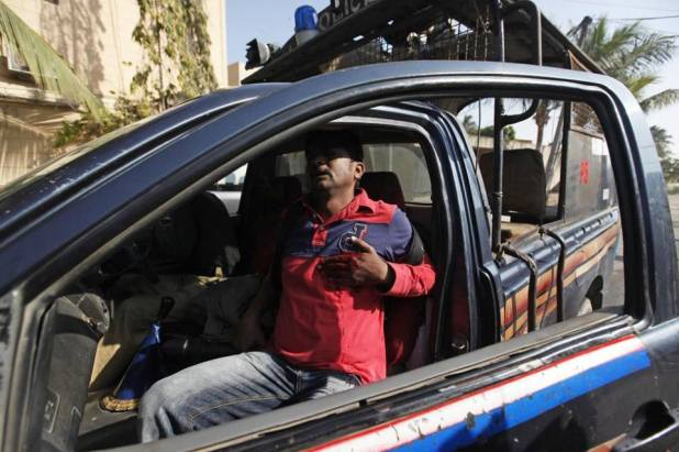 Asif Hassan, a photographer with French news agency Agence France-Press (AFP), sits in a police vehicle after being shot in his chest during a protest organised by Islami Jamiat-e-Talaba, the student wing of religious political party Jamaat-e-Islami (JI), against the satirical French weekly Charlie Hebdo, which featured a cartoon of the Prophet Mohammad as the cover of its first edition since an a... See more
