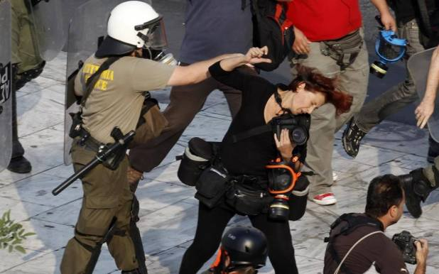 A riot policeman punches Greek photojournalist Tatiana Bolari during a demonstration in Athens' Syntagma (Constitution) square October 5, 2011. Police officers attacked several members of the press covering the protests, injuring at least two members of the media. REUTERS/Yannis Behrakis