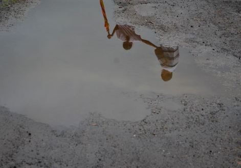 A puddle in Khardi reflects images