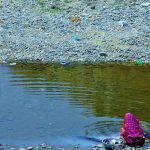 Indian woman washes vessels and clothes in a stream