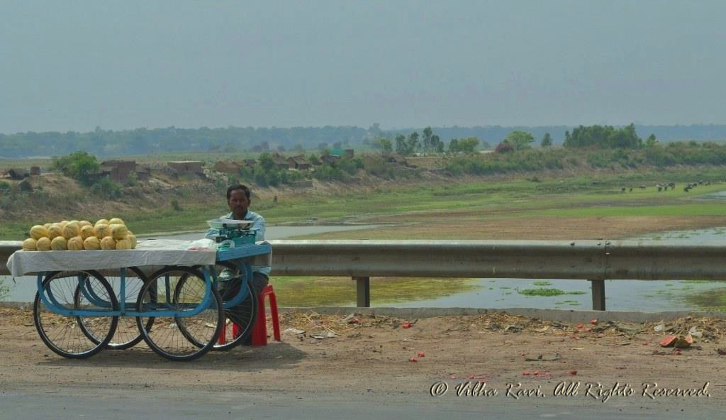 Fruit vendor on highway with Ganges in background