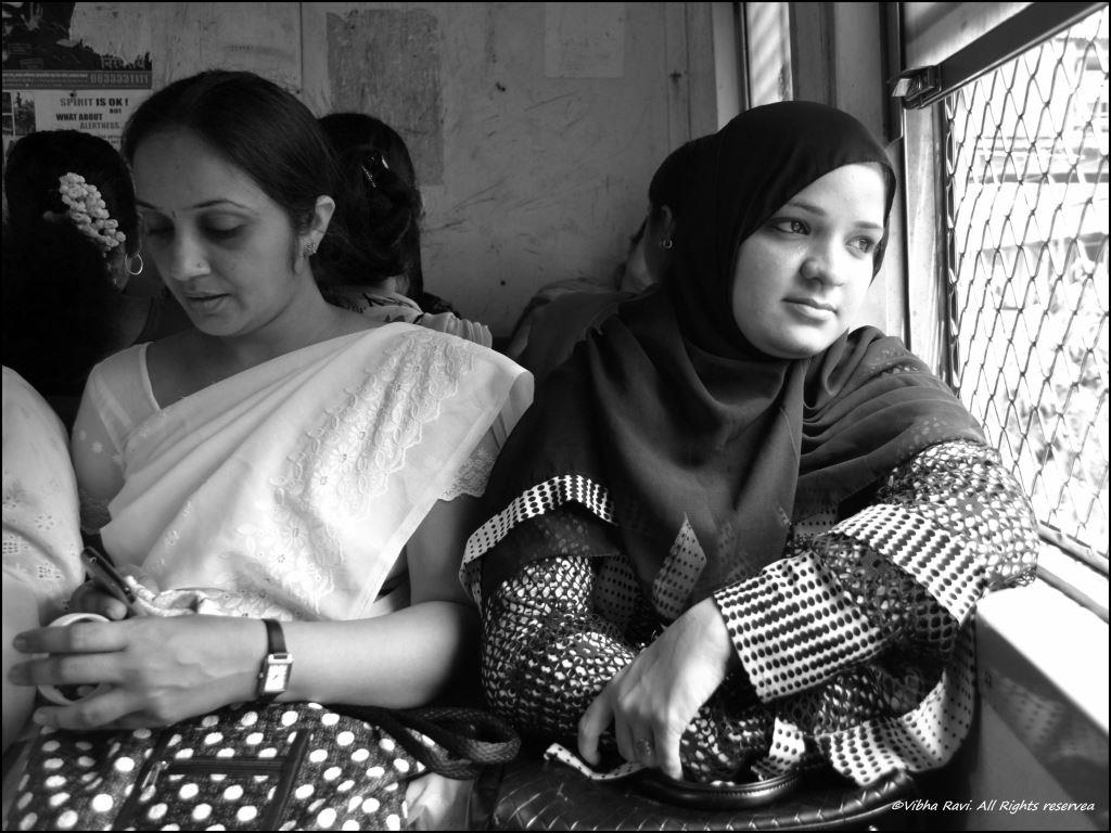 A Gujarati lady and a Muslim woman share space in a Mumbai local train