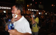 Admiralty Centre. Moments after tear-gas is deployed. A man takes off his mask to breathe and doses himself with water.