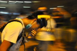 Outside Admiralty bus station. A young man suffers from tear-gas and bends over to recover