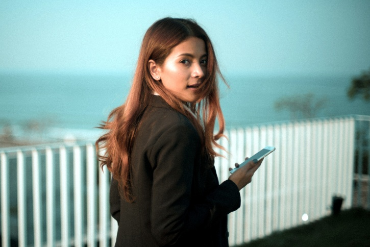 Free Picture Woman Looking Back Holding Smartphone