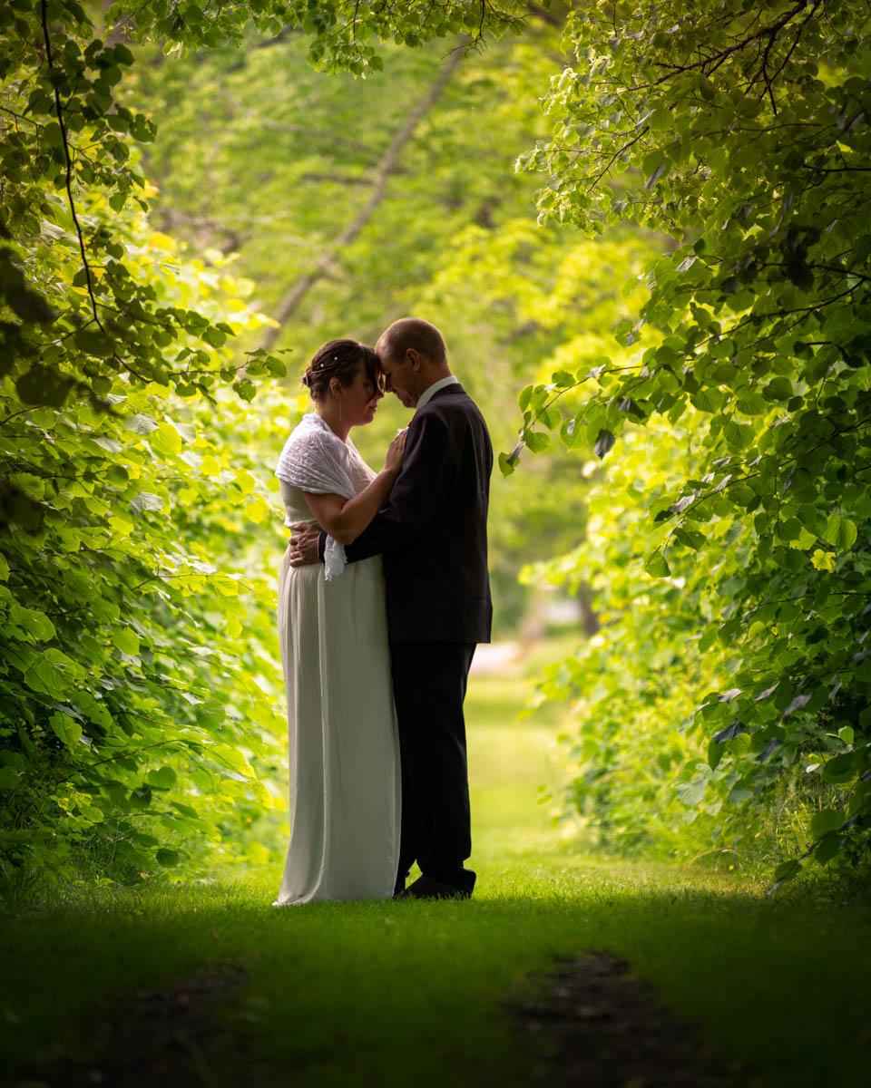 Bröllopspar håller om varandra omgivna av träd