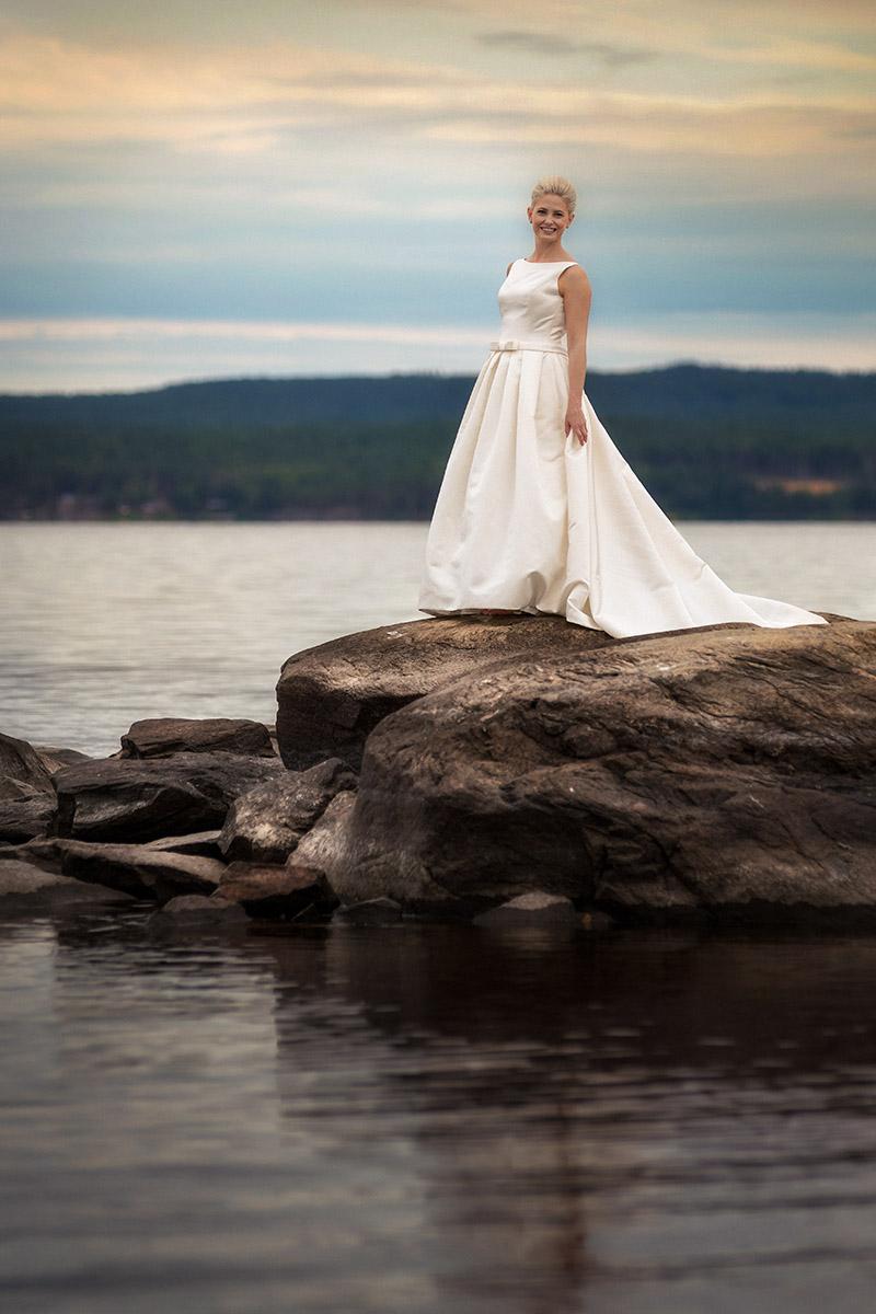 Brud står på sten i bröllopsklänning vid Glafsfjorden Arvika
