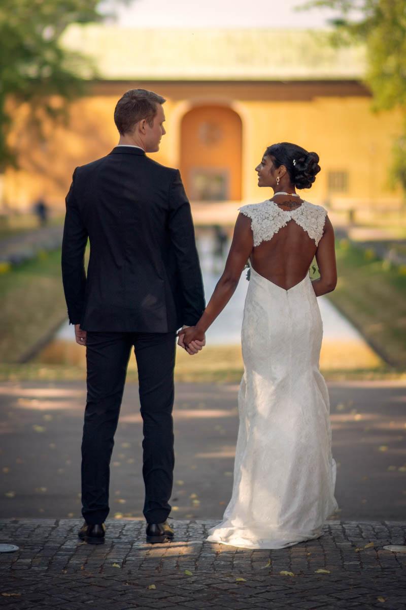 Bröllopspar håller varandras hand och tittar på varandra med ryggen mot kameran.