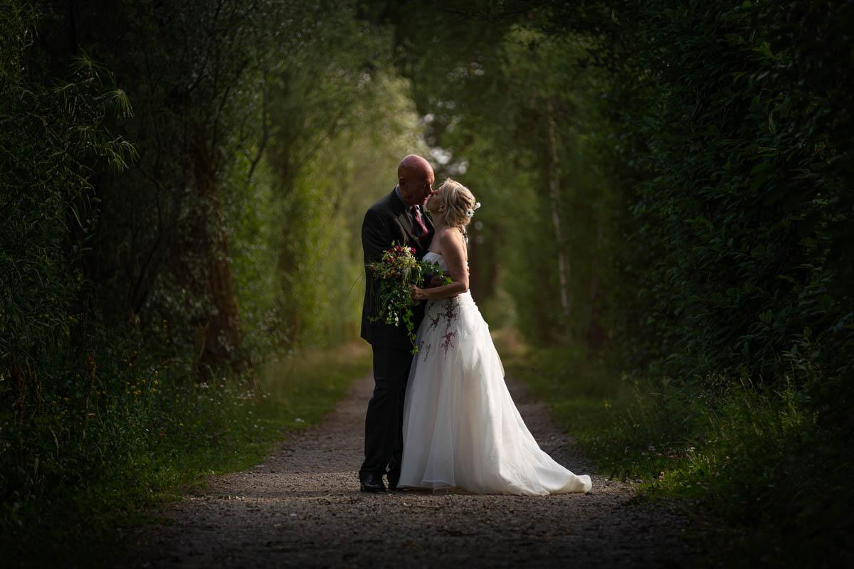 Bröllopspar står i en allé och kysser varandra på Viksholmen i Arvika