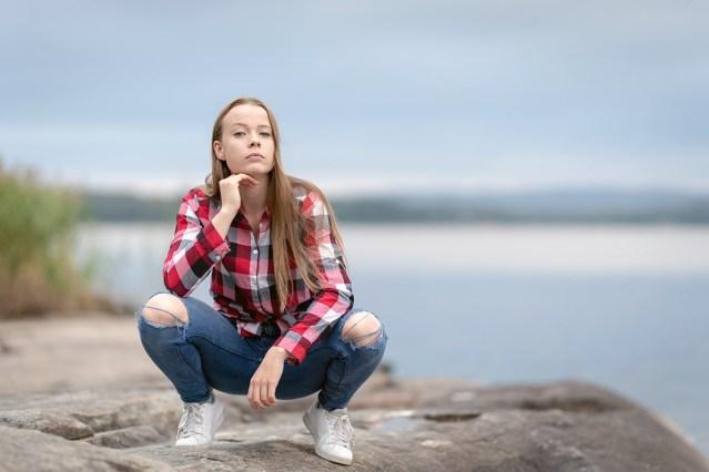 tonårig kvinna sitter på huk vid Glafsfjorden Arvika