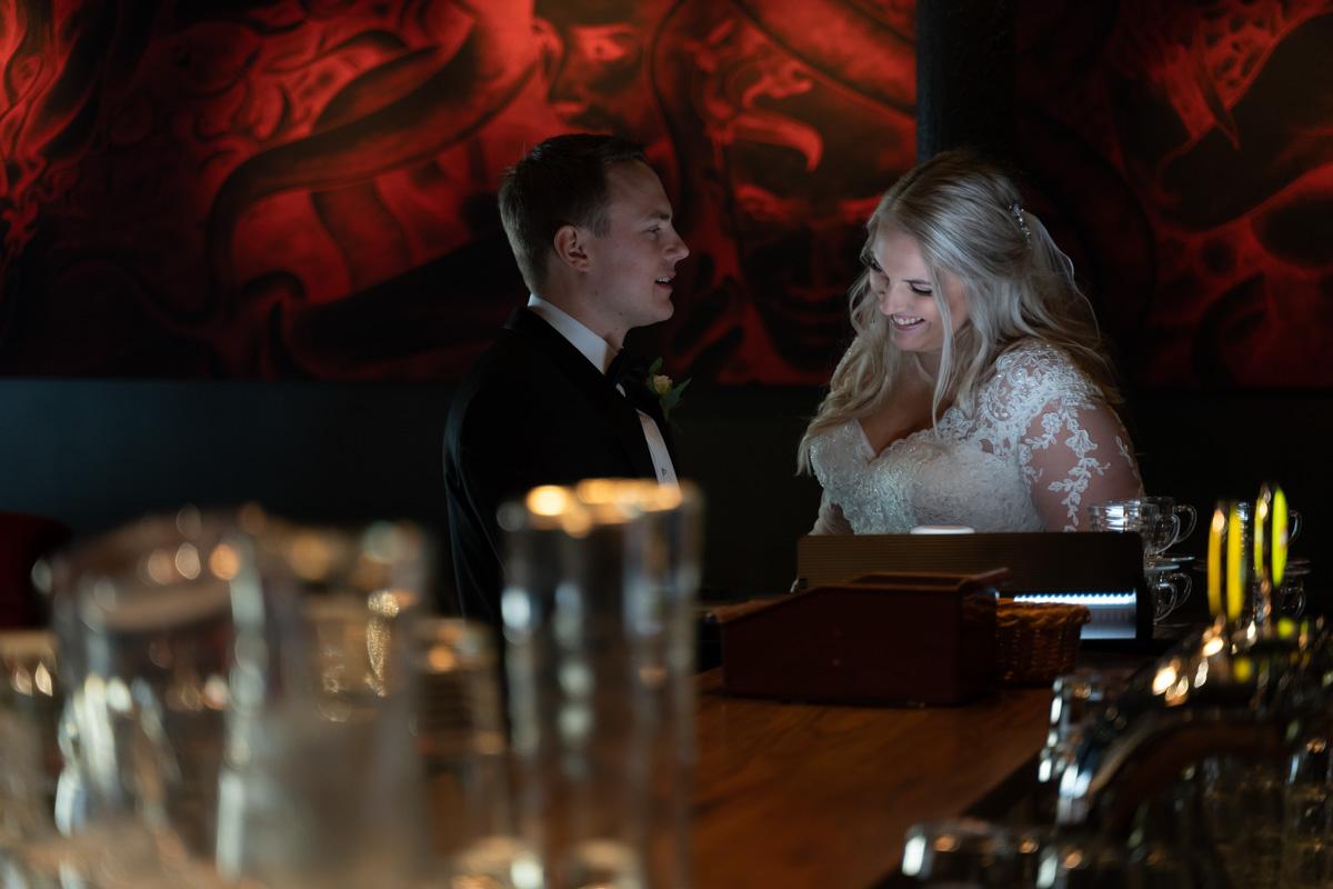 Bröllopspar skojar med varandra vid bardisken på restaurang Häll i Arvika