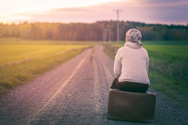 kvinna sitter på resväska på en väg och väntar