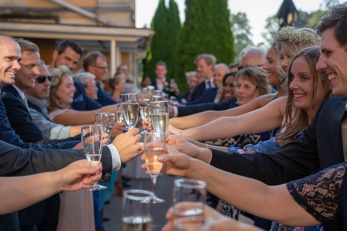 Bröllopsgäster står på rad med höjda glas och skålar för bröllopsparet