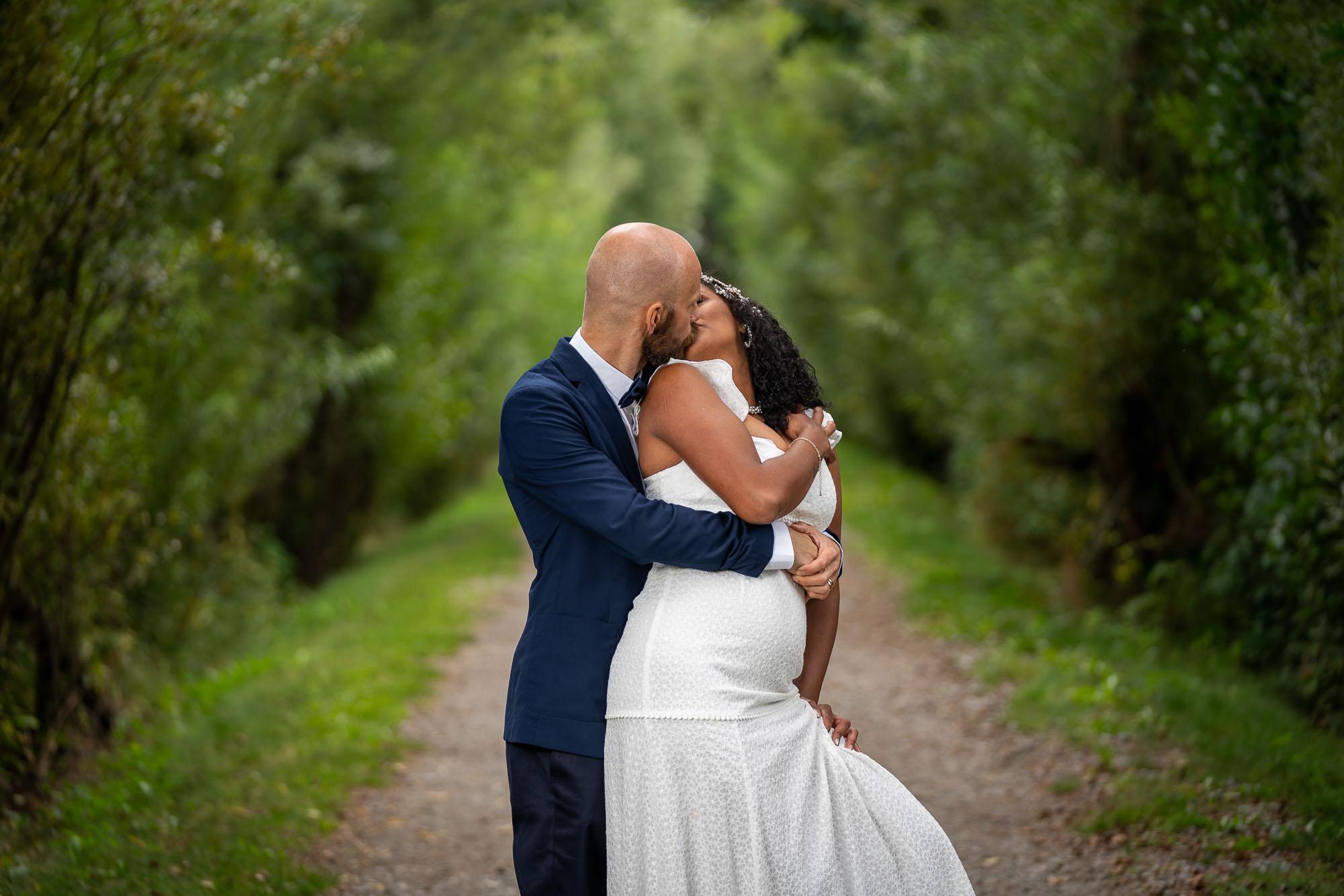 bröllopspar kysser varandra passionerat i en allé på Viksholmen i Arvika