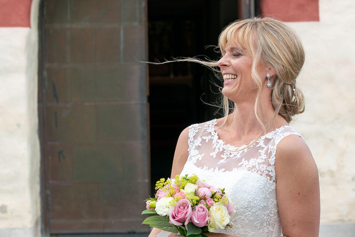 Bruden håller om brudbukett och skrattar utanför Gräsmark kyrka