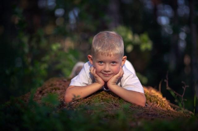 liten pojke ligger på magen på sten med händer mot huvud Kjörselviken Arvika