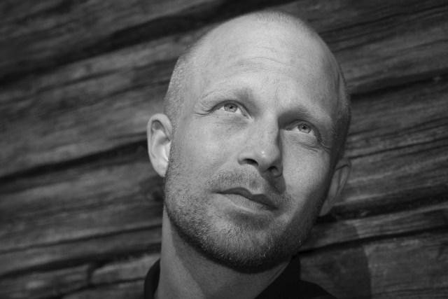 svart vitt porträtt av man med timmerstockar i bakgrunden i Gunnarskog