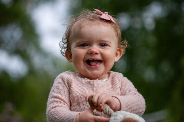 glad liten flicka med nallen i handen i stadsparken i Arvika