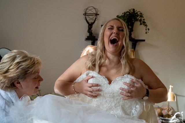 bruden skrattar när hon får hjälp att klä på sig brudklänning på Scandic hotell i Arvika