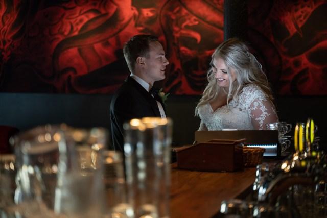 bröllopsparet skrattar vid bardisken på restaurang Häll i Arvika