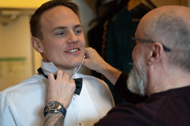 Brudgummen får hjälp att knyta slipsen på hotellrummet Scandic Hotell Arvika