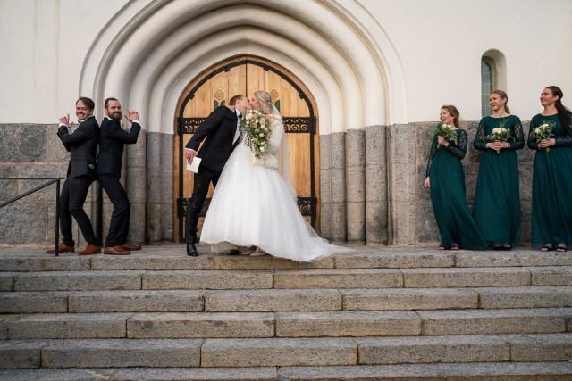 Bröllopsparet med brudtärnor och marskalker kysser varandra på trappan till Trefaldighetskyrkan i Arvika