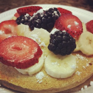 Whole-wheat pancakes, fruit and a dusting of powdered sugar.