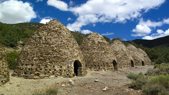 The Charcoal Kilns in Death Valley. These ten beehive shaped masonry structures, about 25 feet high, were completed in 1877 by the Modock Consolidated Mining Company to provide a source of fuel suitable for use in two smelters adjacent to their group of lead-silver mines in the Argus Range west of Panamint Valley, about 25 miles distant from the kilns.