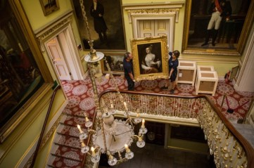 LONDON, ENGLAND - JUNE 29: (IMAGE EMBARGOED FOR USE UNTIL Wednesday 1st July 2015) Art technicians move Titian's Mistress (c.1560) at Apsley House on June 29, 2015 in London, England. Three paintings which had previously been attributed to followers of Titian have been revealed to be been created by the 16th century Venetian artist. These Titians will be revealed at a new English Heritage exhibition 'Titian at Apsley House' which opens on July 1. (Photo by Rob Stothard/Getty Images)