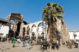 People sit around in a central square in Damascus. Ruins of ancient roman structures can be seen.