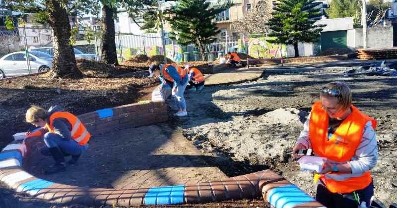 Volunteers wearing work vests painting brick walls in the play space