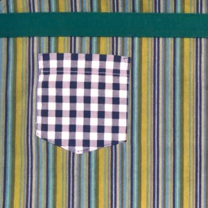 Close up image of a blue gingham pocket on a blue striped background