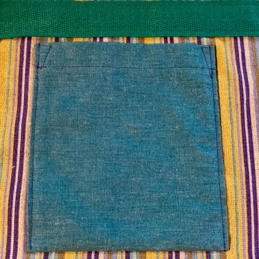 Close up image of a solid teal pocket on a blue striped background