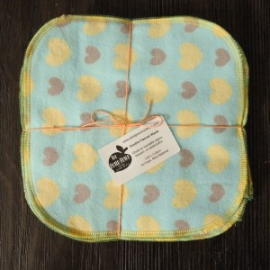 square of teal fabric with yellow and grey hearts