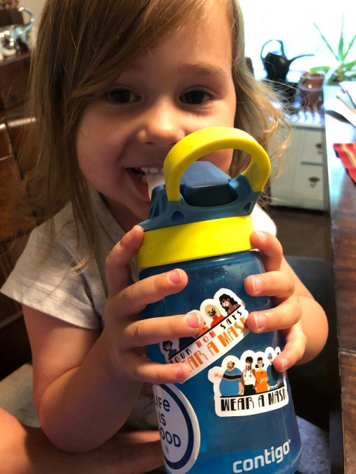 "A child with a water bottle with two ""wear a mask"" stickers"