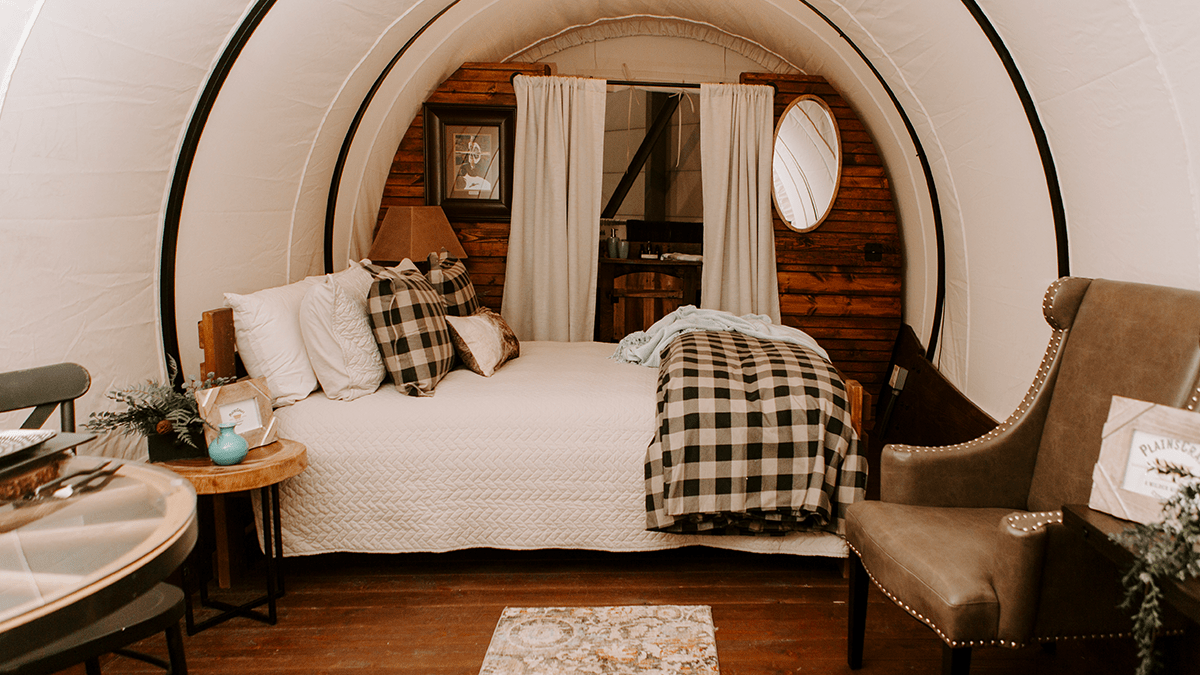 Interior of a luxury covered wagon, bed is made and bathroom is in the background